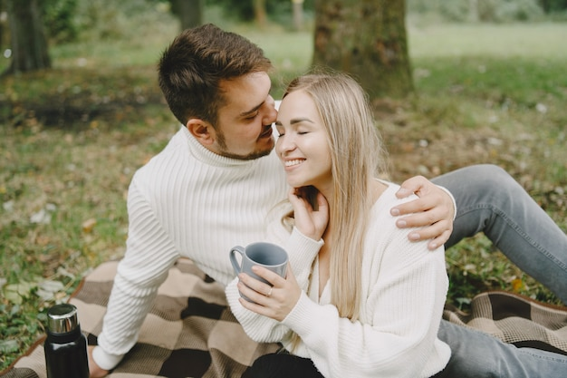 Люди в парке. женщина в коричневом пальто. мужчина в белом свитере. пара на пикнике.