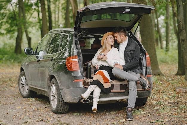 공원에있는 사람들. 흰색 스웨터에 여자입니다. 자동차 트렁크에있는 사람들.