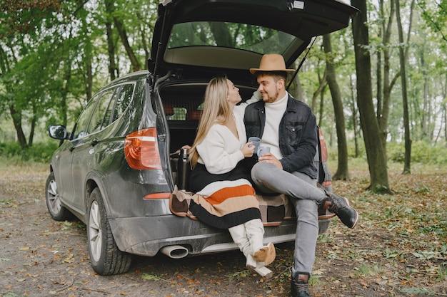 Люди в парке. женщина в белом свитере. люди в багажнике машины.