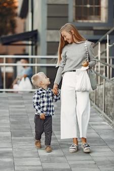 夏の街の人々。息子と母。灰色のセーターを着た女性。