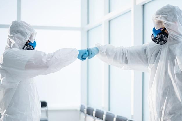 Люди в костюмах биологической опасности приветствуют друг друга. концепция охраны здоровья.