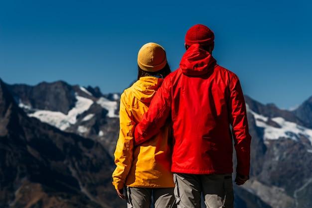 산, 후면보기의 배경에 화려한 재킷을 입은 사람들. 활동적인 커플이 하이킹에 종사하고 있습니다. 젊은 부부가 추적에 종사하고 있습니다. 등산. 산속의 사람들