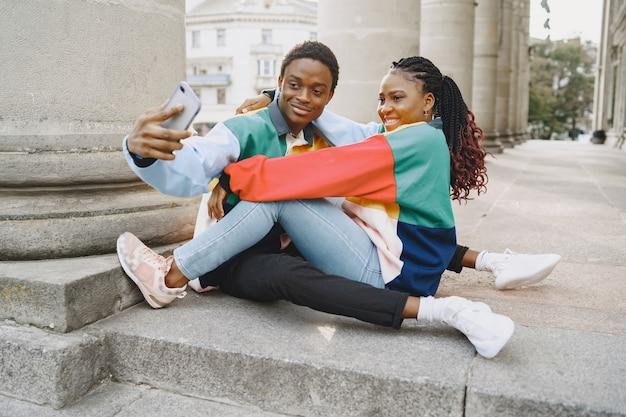 同一の服を着た人。秋の街のアフリカのカップル。座って電話を使う人。