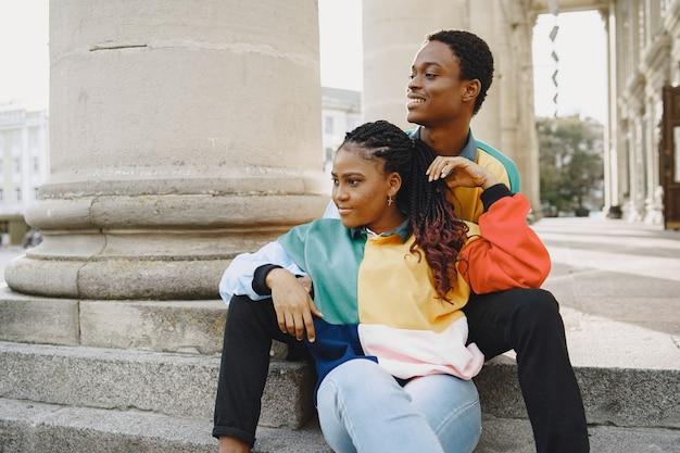 同一の服を着た人。秋の街のアフリカのカップル。通りに座っている人。