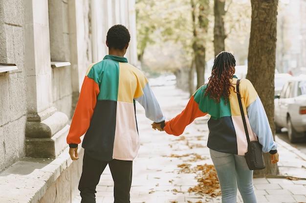 同一の服を着た人。秋の街のアフリカのカップル。