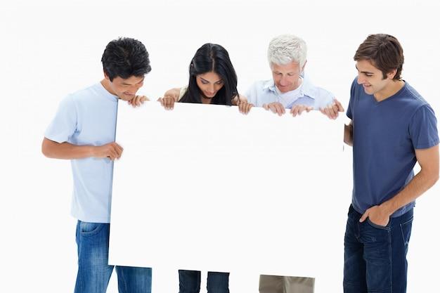 Люди в джинсах, держащие и смотрящие большой знак