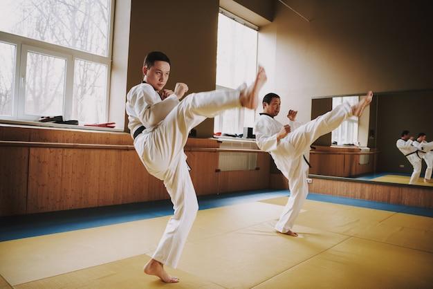 Люди в кимоно отрабатывают стойки с мма.
