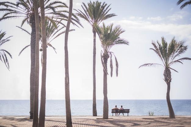 一緒に地平線を見ている愛と関係の人々は、いくつかの熱帯のヤシの下で海の前のベンチに座っています。仕事の後に休むカップルのために一緒に休暇を楽しんでください