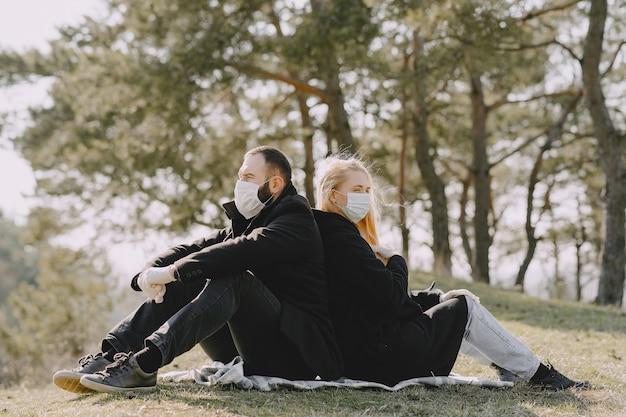 森に座っている仮面の人々