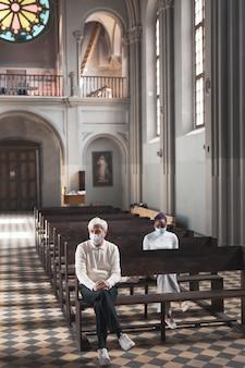 Люди в масках сидят на скамейке в старой красивой церкви и молятся