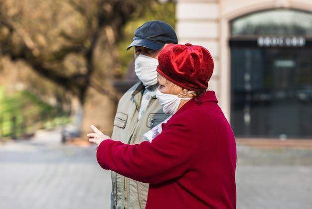 路上で医療用マスクを着用している人々は、コロナウイルスの流行中に彼らのビジネスについて急いでいます。高齢者の幸せなカップル