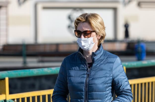 路上で医療用マスクを着用している人々は、コロナウイルスの流行中に彼らのビジネスについて急いでいます。若い女性