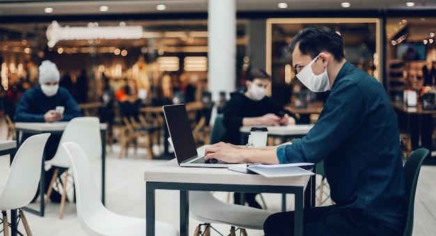 푸드 코트에서 노트북을 사용하는 보호 마스크를 쓴 사람들