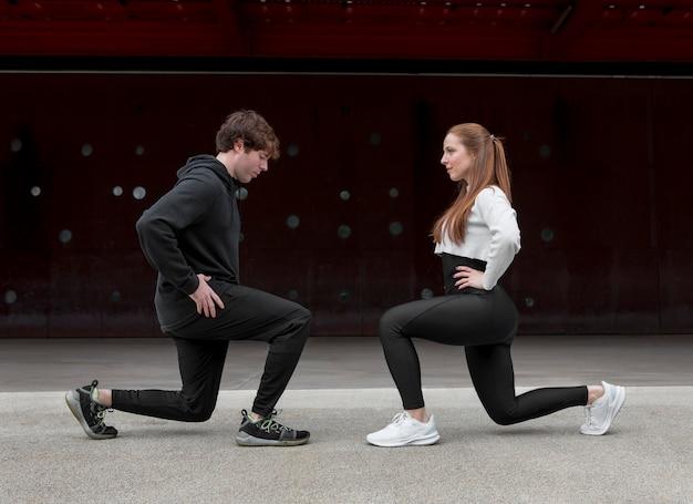 Люди в спортивной одежде тренируются на открытом воздухе