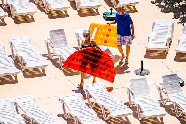 여름철에 사람들과 성인 시니어 백인 coiple과 함께 수영 풀에 다가가는 컬러 트렌디 한 lilos와 함께 여름 야외 레저 활동에서 함께 휴식을 취하십시오.