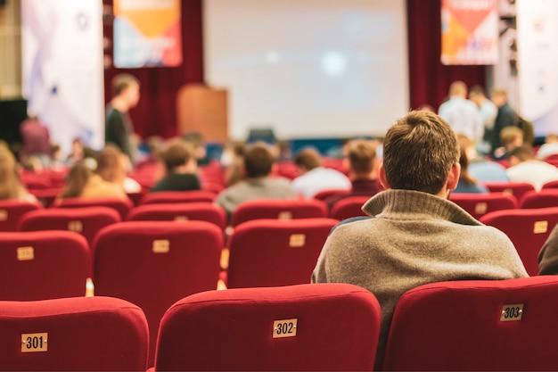 Люди в зрительном зале на бизнес-конференции. человек, сидящий сзади и наблюдающий