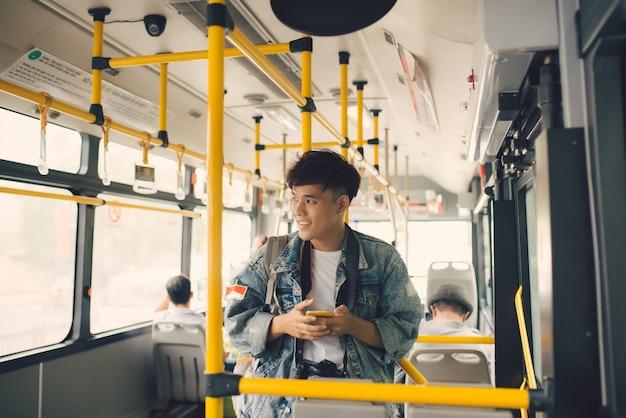 버스에 있는 사람들. 대중 교통에서 스마트폰을 사용하는 아시아 남자