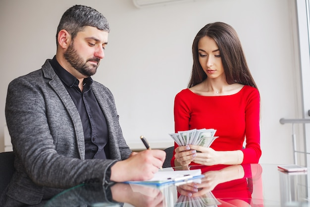 Люди в офисе, считая банкноты