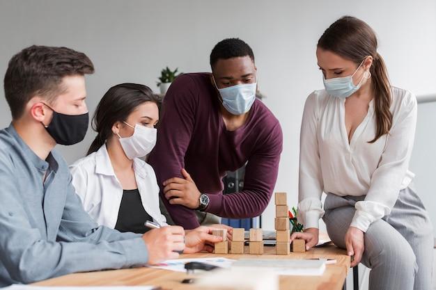 Люди в офисе во время пандемии собираются вместе