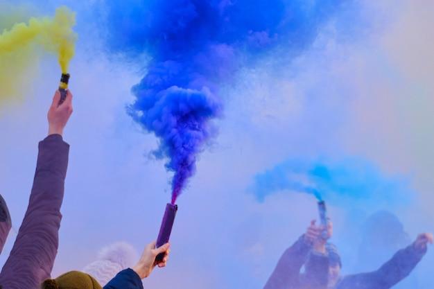 Люди в руках на празднике держат разноцветные фейерверки с дымом.