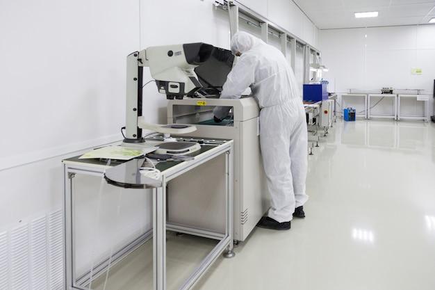 실험실에서 일하는 흰색 격리 의상을 입은 사람들
