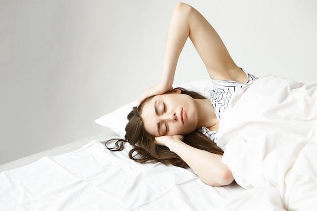 人々、不眠症、睡眠障害の概念。彼女の部屋の白い寝具の上に横たわって、頭をマッサージし、長い仕事の後に眠ろうとしている美しい悲しい若い黒髪の女性の屋内ショット