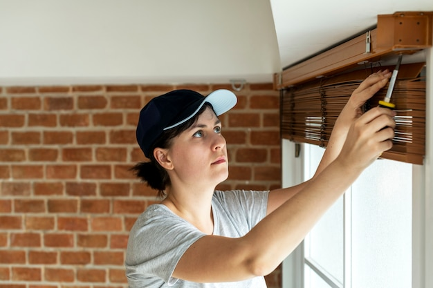 People installing window curtain