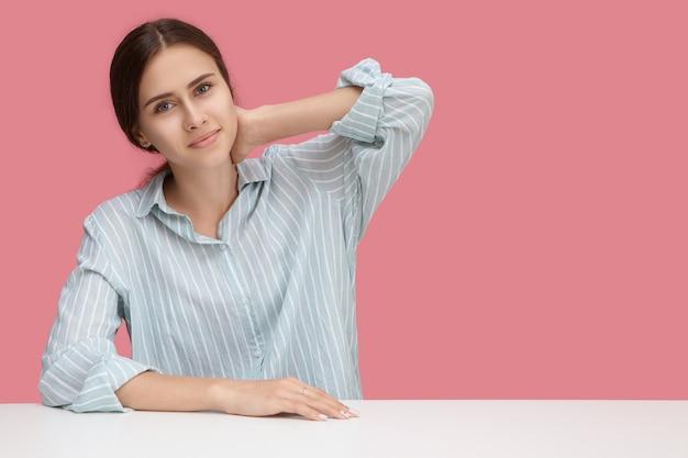 Люди, работа, карьера и концепция занятия. привлекательный положительный молодой европейский служащий женщины в полосатой рубашке работая в офисе. девушка довольно милая студент сидит за белым столом, протягивая руки