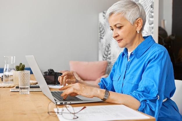 Люди, работа, род занятий, возраст и занятость. внутреннее изображение красивой седой женщины на пенсии, ищущей удаленную работу с помощью портативного компьютера. зрелая женщина-фотограф печатает на ноутбуке