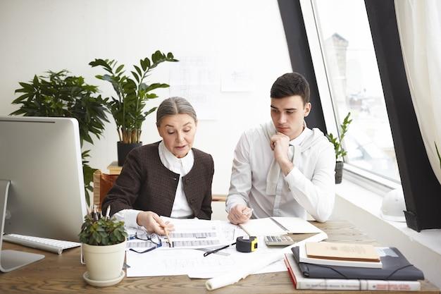 Люди, работа, работа в команде и концепция сотрудничества. два профессиональных коллеги-инженера сидят за столом с чертежами, компьютером и инженерными инструментами, обсуждают планы и идеи, серьезно выглядят