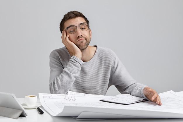 People, job, tiresome and overwork concept. bored sleepy male engineer working on blueprints