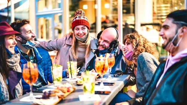 Люди присоединяются к коктейлям в счастливый час в баре-ресторане под открытым небом
