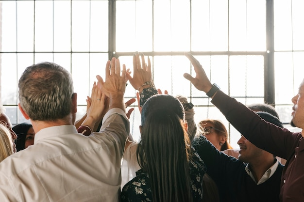 People joining hands in the air at a meeting