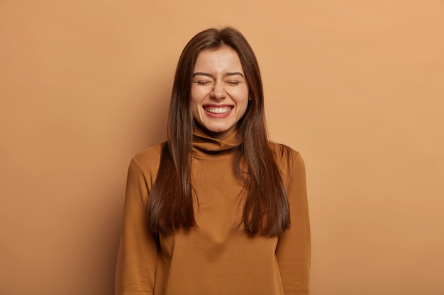 People and joy concept. overjoyed dark haired adult woman laughs happily with closed eyes, talks casually with friend, cannot hold laughter, wears casual turtneck, isolated on brown wall