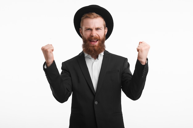 People, joy, happiness and success concept. happy confident young bearded red haired businessman wearing stylish round had and suit exclaiming winningly and excitedly, raising clenched fists