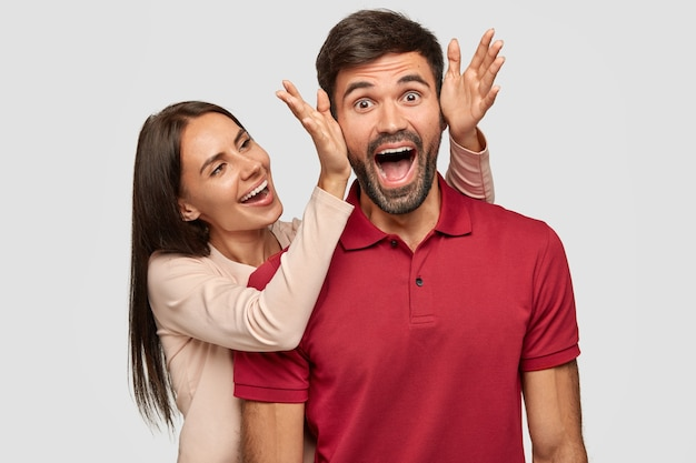 People, joy, pleasant moment in life. overjoyed brunette european young female stands near her boyfriend, going to cover eyes and make surprise, have fun together, isolated over white wall.
