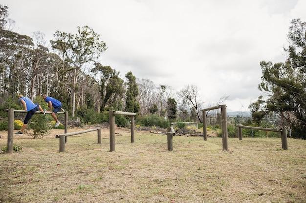 Люди прыгают через препятствия во время полосы препятствий в учебном лагере