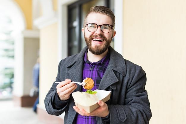 人、ジャンクフード、食事、ライフスタイル – 街の通りでコーヒーカップとサンドイッチを食べたり飲んだりする若者