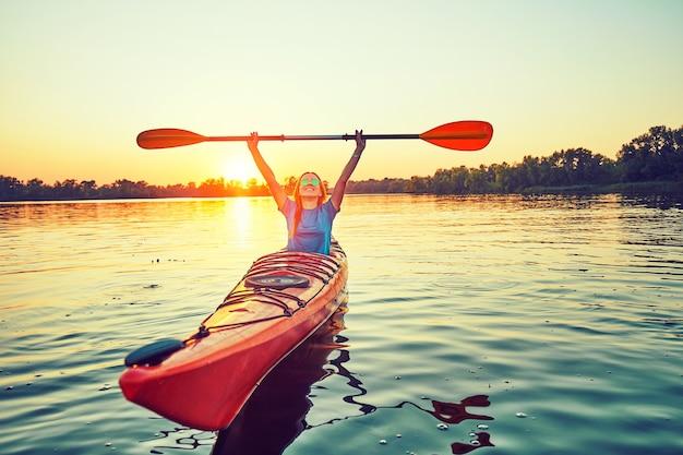 백그라운드에서 일몰 동안 사람들은 카약. 여가 시간에 즐겁게 보내세요.