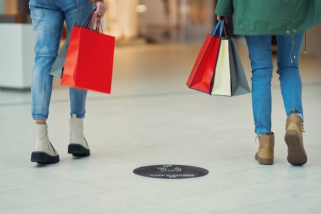 ショッピングモールで買い物をしながら社会的距離を保つ人々