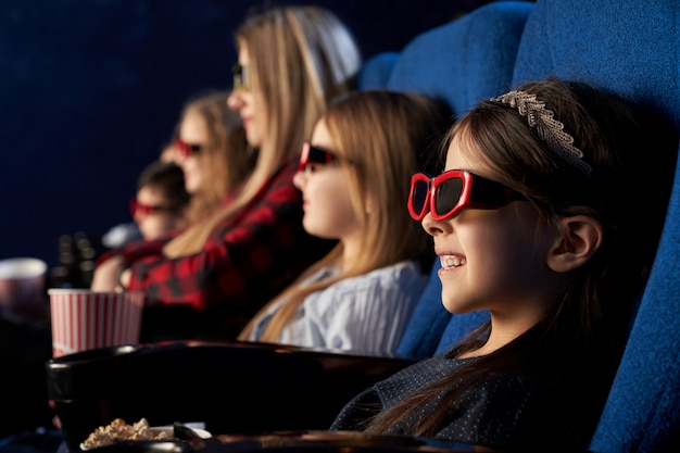 People, kids watchng movie in 3d glasses in cinema.