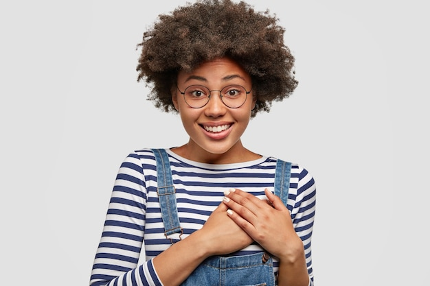 Concetto di persone, gentilezza e sentimenti. la femmina afroamericana attraente soddisfatta tiene le mani sul cuore, esprime simpatia, indossa un maglione a righe con salopette, isolato sopra il muro bianco