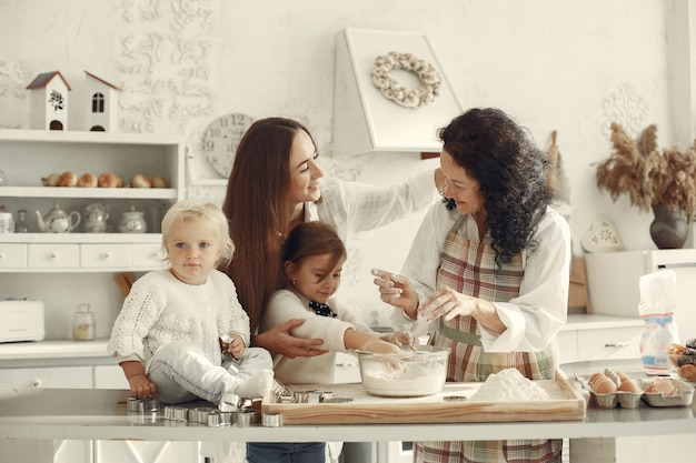 People in a kitchen. family prepare cake. adult woman with daughter and grandchildren.