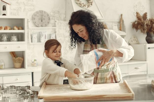 Persone in una cucina. nonna con la piccola figlia. la donna adulta insegna alla bambina a cucinare.