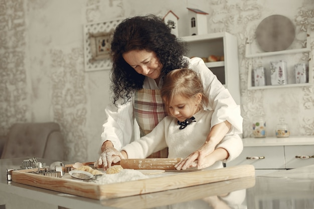 People in a kitchen. grandmother with little daughter. adult woman teach little girl to cook.