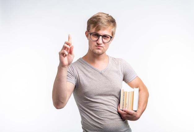 人、知識、教育の概念-本を手に持った灰色のtシャツを着た学生男性の肖像画。