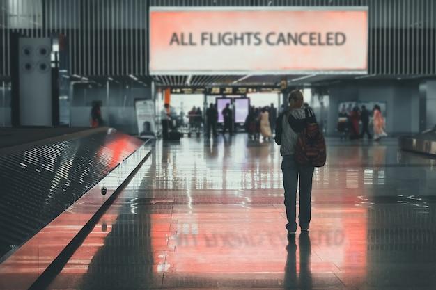 人々は空港を去ります。女の子は空港ターミナルを歩きます。すべてのフライトがキャンセルされます。 covid-19の発生により、航空機の発着を禁止します。航空業界の問題と危機。