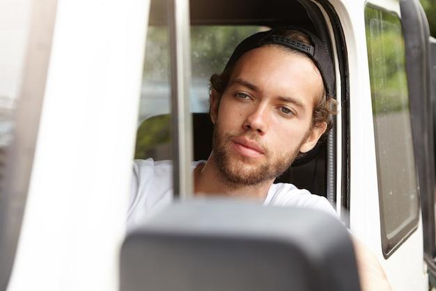 人、レジャー、冒険、極端なコンセプト。白い四輪駆動車を運転するファッショナブルな若いひげを生やした冒険家