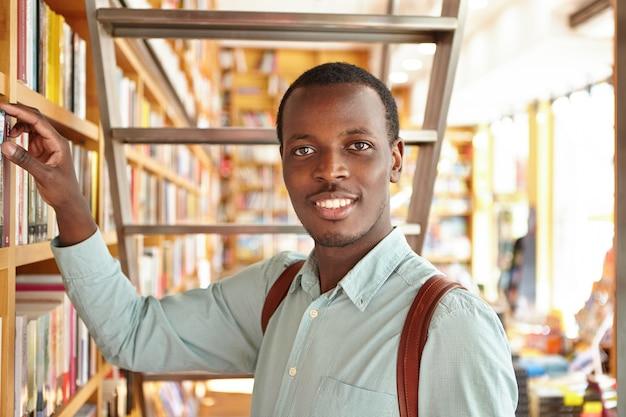 人、レジャー、教育。研究をしながら図書館で本を探している好奇心旺盛なアフロアメリカンの学生。黒の観光客が海外での休暇中に書店の棚から慣用句を選択