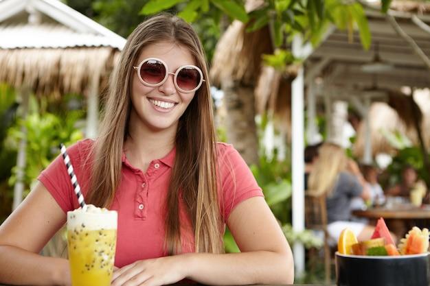 人、レジャー、ライフスタイルのコンセプトです。彼女の休暇中に幸せな日を楽しみながら陽気な表情を持つスタイリッシュな丸いサングラスでファッショナブルな女性